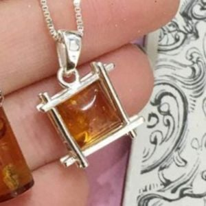Sterling Silver Baltic Amber Pendant Encaged in a Lattice Box design measuring approximately 23 mm long (E