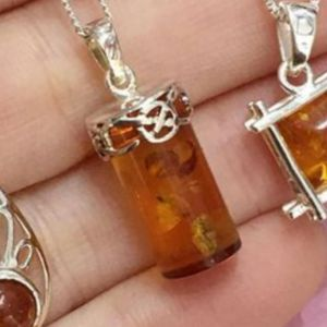 Sterling Silver Baltic Amber Pendant with a Geometric triangle design measuring approximately 24 mm long